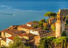 Blick über die Bastion, die Stadt und den Hafen von Castiglione della Pescaia bei Sonnenaufgang, Toskana, Italien