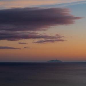 Wolken über der Insel Montechristo im tyrrhenischen Meer vor der Küste der Toskana in der Abenddämmerung, Maremma, Italien