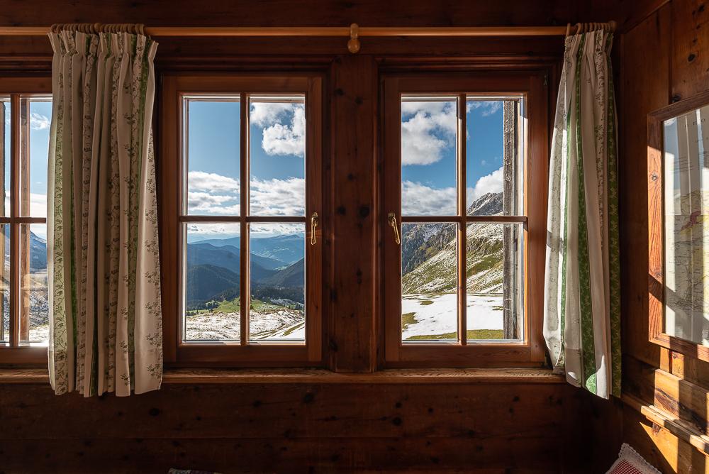 Ausblick durch ein Fenster in der Gaststube der Schlüterhütte auf das Villnößtal und die Sarntaler Alpen, Dolomiten, Südtirol, Italien