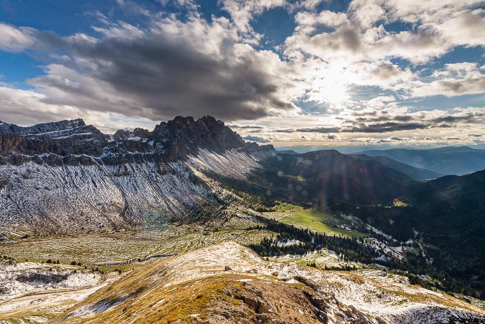 Abendsonne strahlt durch Wolken auf eine bunte Herbstlandschaft der Dolomiten mit Gampenalm, Geisleralm, Raschötz, Seceda und Geislerspitzen der Puez-Geisler-Gruppe, Villnößtal, Südtirol, Italien