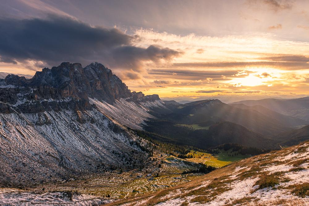 Die verschneiten Geislerspitzen der Puez-Geisler-Gruppe oberhalb des Villnößtals leuchten golden im Gegenlicht der Abendsonne in den Dolomiten im Herbst, Südtirol, Italien