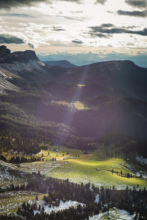 Sonne strahlt durch Wolken auf eine Herbstlandschaft der Dolomiten mit Gampenalm, Geisleralm, Raschötz und Seceda der Puez-Geisler-Gruppe, Villnößtal, Südtirol, Italien