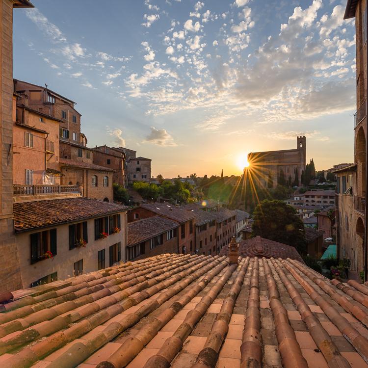 Die Abendsonne bringt die Altstadt von Siena zum Leuchten und verschwindet hinter der Basilica di San Domenico, Siena, Toskana, Italien