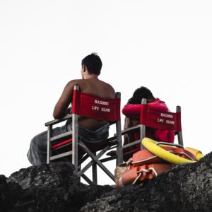 Die Bademeister der Nachtschicht am Bagno delle Donne sitzen auf Stühlen auf den Felsen, Talamone, Toskana, Italien