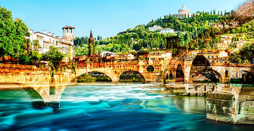Die römische Ponte Pietra über dem Fluß Etsch in der Altstadt von Verona vor mediterraner Landschaft in der Morgensonne, Venetien, Italien