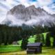 Heuhütten auf einer blühenden Almwiese vor dem Zwischenkofeltal und den Felswänden des Somamunt der Puez-Geisler-Gruppe, Campilltal Dolomiten, Südtirol, Italien
