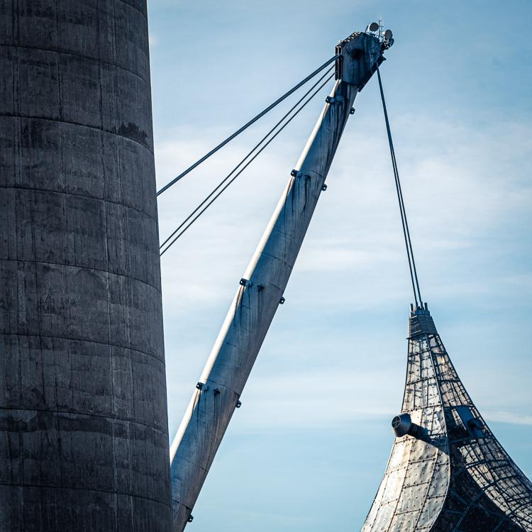 Betonwand des Olympiaturms vor einem Stahlträger mit der Spitze des Zeltachs der Olympia-Schwimmhalle, München, Deutschland