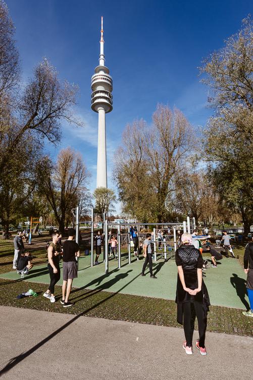 An einem sonnigen föhnigen Sonntag im November trainieren junge Menschen draußen im Olympiapark von München, Deutschland