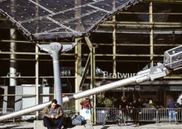 Mann sitzt auf einer Betonbefestigungen der Stahlseile des Zeltdachs der Olympiahalle im Olympiapark, München, Deutschland