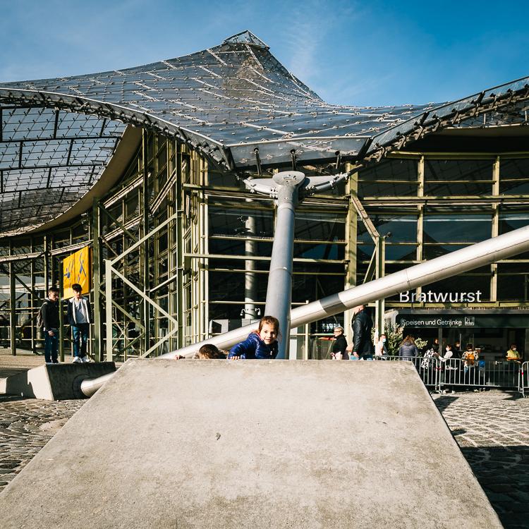 Kinder spielen auf den Betonbefestigungen der Stahlseile des Zeltdachs der Olympiahalle im Olympiapark, München, Deutschland