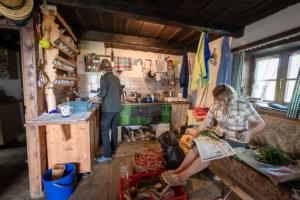 Zwei Frauen im Innern der Almhütte der Roßalm beim Kochen und dem Binden von Kränzen für den Almabtrieb, Chiemgau, Bayern, Deutschland