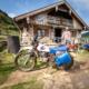 Geländegängiges Motorrad und sein Fahrer an der Roßalm nach dem Transport von Getränken zur Hütte, Bayern, Deutschland