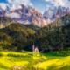 Herbstliche Landschaft der Dolomiten mit der Ranui-Kapelle in Villnöß vor Bergwäldern und den Felswänden der Geislerspitzen im Sonnenschein, Puez-Geisler-Gruppe, Südtirol, Italien