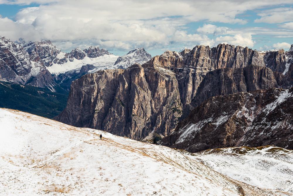 Zwei Wanderer beim Aufstieg zum Zendleser Kofel vor einer verschneiten Landschaft mit den Felswänden der Puez-Spitzen und dem Fanes-Sennes-Prags Bergmassiv in den Dolomiten im Herbst, Südtirol, Italien