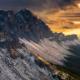 Die verschneiten Geislerspitzen vor dramatischen Wolken leuchten golden in der Abendsonne beim Sonnenuntergang in den Dolomiten im Herbst, Südtirol, Italien