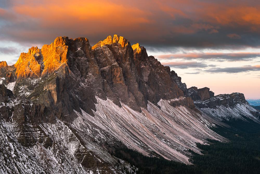 Wolken und die Felsen der Geislerspitzen leuchten golden im Sonnenlicht bei Sonnenaufgang über der Puez-Geisler-Gruppe und den Dolomiten, Villnößtal, Südtirol, Italien