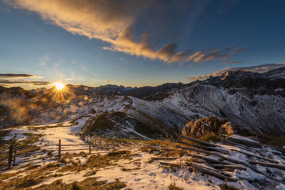 Die Morgensonne kommt über den Gipfeln der Fanes-Sennes-Prags-Gruppe der Dolomiten hervor und scheint auf das schneebedeckte Kreuzkofeljoch, Puez-Geisler-Gruppe, Südtirol, Italien