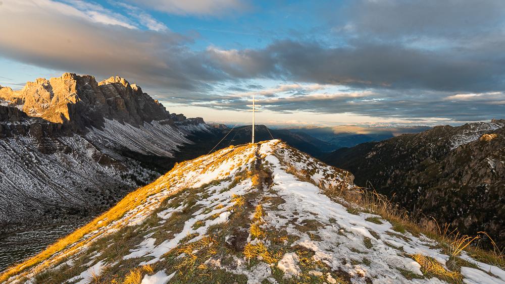 Gipfelkreuz des Zendleser Kofels mit den Geislerspitzen und der Villnößer Geisler Gruppe oberhalb des Villnößtals in den Dolomiten leuchtet im Sonnenschein bei Sonnenaufgang im Herbst, Südtirol, Italien