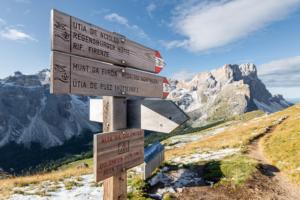 Hölzener Wegweiser in herbstlicher Landschaft in der Puez-Geisler-Gruppe der Dolomiten mit Geislerspitzen, Puezspitzen, Medalgesalm im Sonnenschein bei Sonnenaufgang, Südtirol, Italien