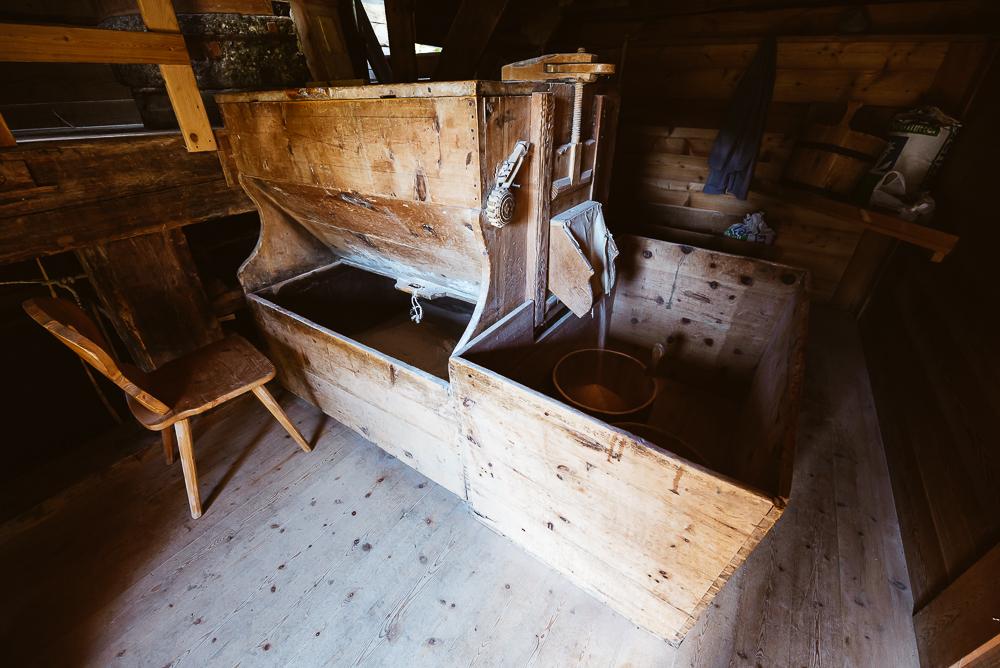 Hölzernes Mahlwerk im Innern der historischen Getreidemühle im Mühlental von Campill, Südtirol, Italien