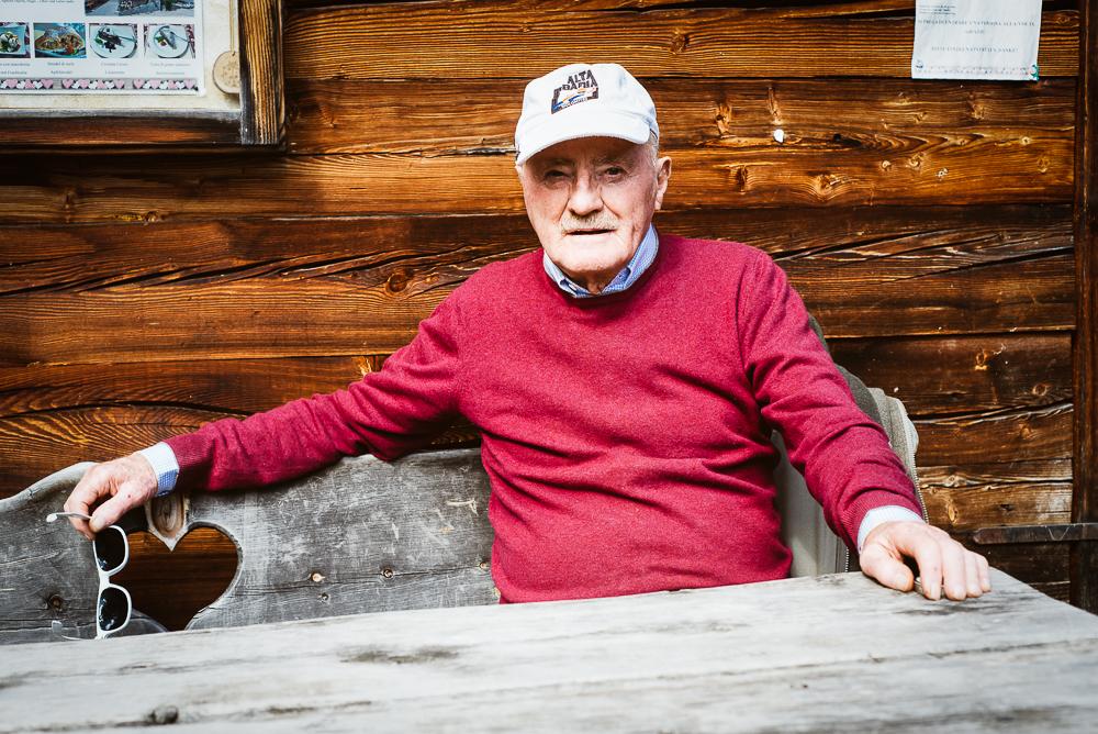 Portrait eines älteren Mannes vor der rustikale Holzfassade einer historischen Getreidemühle im Mühlental von Campill, Südtirol, Italien