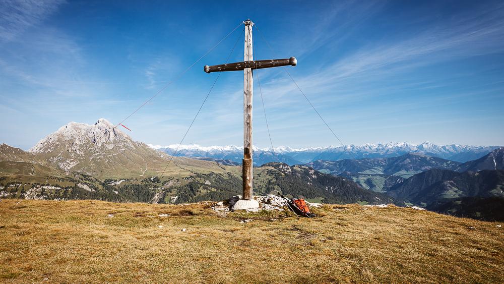 Gipfelkreuz des Zwölferkofels vor einer Herbstlandschaft mit dem Campilltal, dem Peitlerkofel und dem Panorama des Alpenhauptkamms im Herbst im Sonnenschein, Puez-Geisler-Gruppe, Dolomiten, Südtirol, Italien