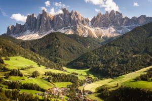 Herbstliche Landschaft der Dolomiten mit dem Ort Villnöß vor Bergwäldern und den Felsgipfeln der Geislerspitzen im Sonnenschein, Puez-Geisler-Gruppe, Südtirol, Italien