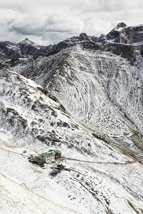 Die Schlüterhütte Rifugio Genova vor verschneiten Bergen und Felsgipfeln der Puez-Geisler-Gruppe in den Dolomiten, Südtirol, Italien