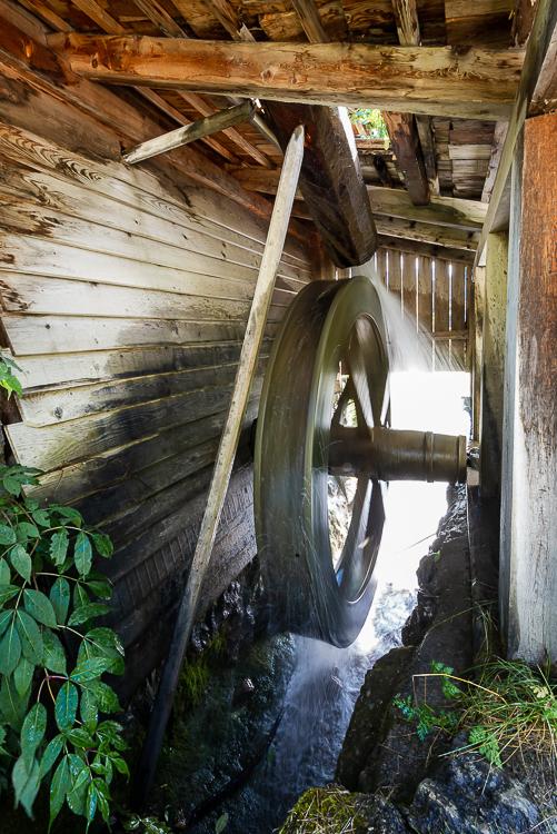 Wasser treibt ein hölzernes Wasserrad einer historischen Getreidemühle im Mühlental von Campill an, Südtirol, Italien
