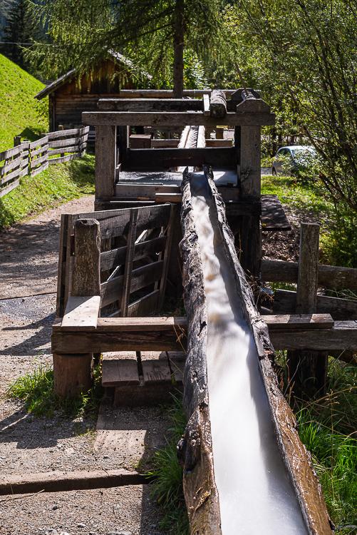 Hölzerne Wasserleitung für das Wasserrad einer historischen Getreidemühle im Mühlental von Campill an, Südtirol, Italien