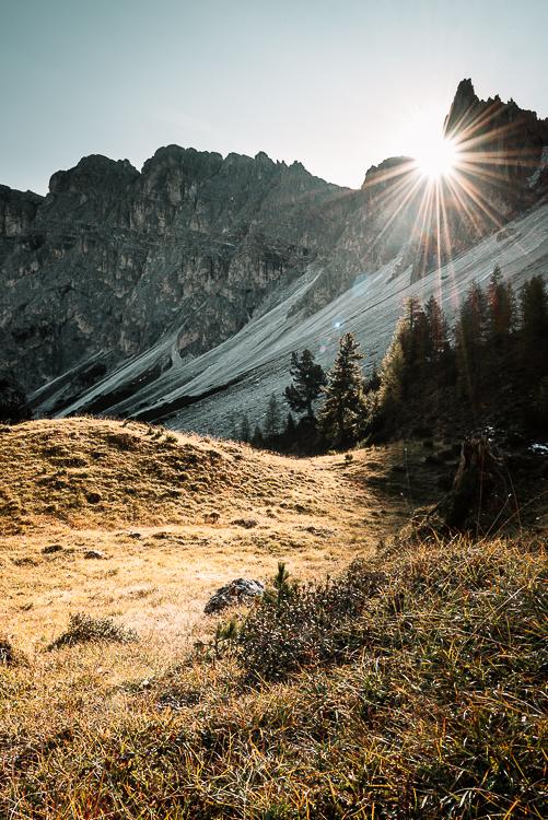 Die Strahlen der Morgensonne zwischen den Felsgipfeln der Puezspitzen bringen die Wiesen des Zwischenkofeltals unterhalb der Alm Antersasc zum Leuchten, Dolomiten Puez-Geisler-Gruppe, Südtirol, Italien