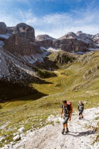 Wanderer im Zwischenkofeltal mit der Alm Antersasc unterhalb der Puezspitzen in der Morgensonne, Dolomiten Puez-Geisler-Gruppe, Südtirol, Italien