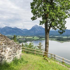 Ausblick von der Burgruine über dem Hopfensee auf die Berge der Ammergauer Alpen mit Schloss Neuschwanstein, Allgäu, Bayern, Deutschland